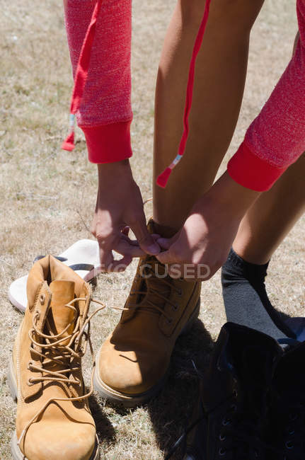 High angle view of female hiker tying shoelace while standing on field — Stock Photo
