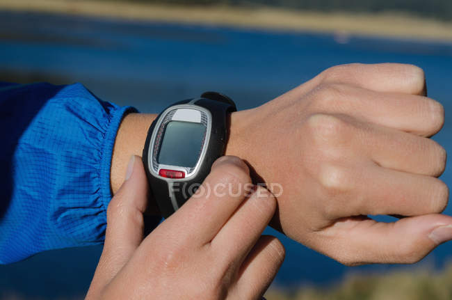 Обрезанное изображение женщины, регулирующей наручные часы в солнечный день — стоковое фото