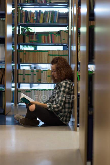 Vue latérale du livre de lecture adolescente tout en étant assis par étagère dans la bibliothèque — Photo de stock