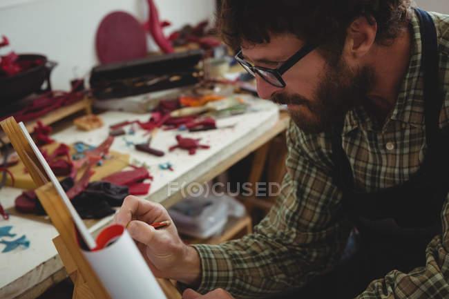 Craftsman drawing sculpture design in workshop — Stock Photo
