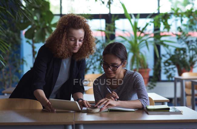 Девушка показывает планшетный компьютер другу во время учебы на рабочем столе в классе — стоковое фото