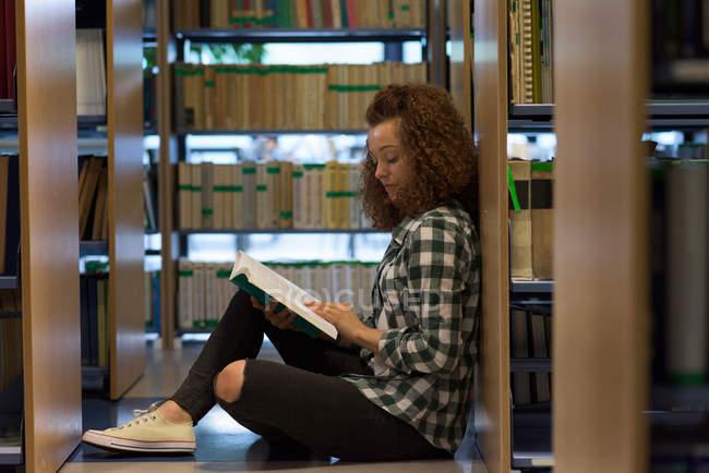Vue latérale d'un livre de lecture pour adolescentes assis près d'une étagère dans une bibliothèque — Photo de stock