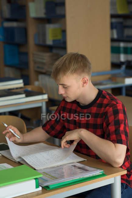 Vue en angle élevé du jeune étudiant mâle étudiant au bureau en classe — Photo de stock