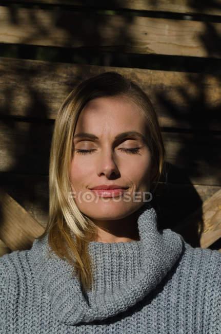 Крупный план женщины-туриста с закрытыми глазами на деревянном заборе — стоковое фото