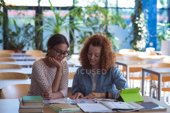 Estudiantes universitarios mujeres que estudian en la mesa de trabajo en el aula - foto de stock