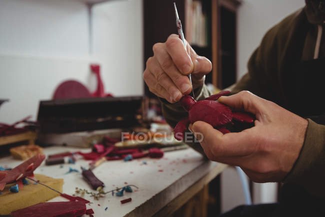 Craftsman working on clay sculpture in workshop — Stock Photo