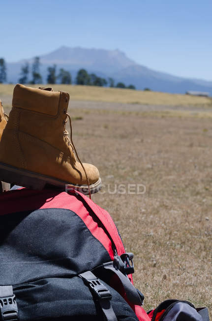 Close up of boots on backpack at field — Stock Photo