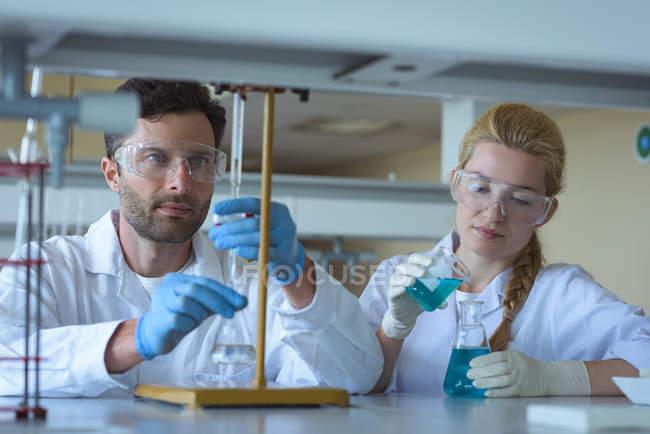 Студенти університетів проводять хімічний експеримент у лабораторії. — стокове фото