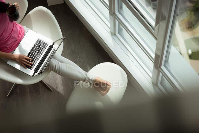 Metà sezione della donna che utilizza il computer portatile in soggiorno — Foto stock