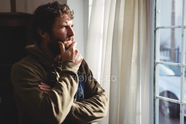 Ремесленник смотрит в окно в мастерской — стоковое фото