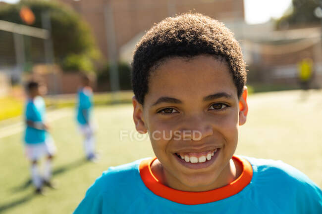 Portrait of a mixed race boy soccer player wearing a blue team strip, standing on a playing field on a sunny day, looking to camera and smiling, with teammates standing in the background — Stock Photo