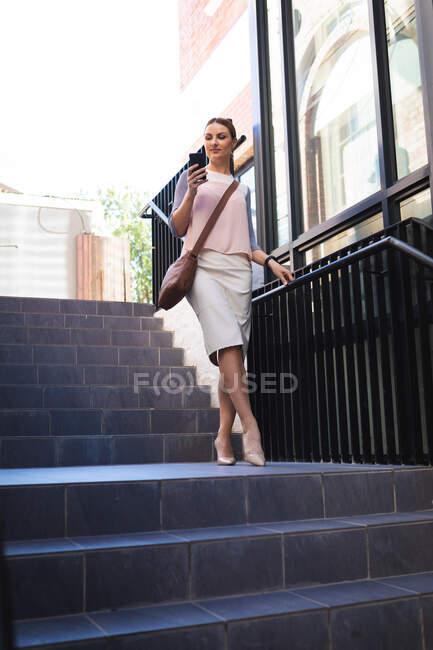 Кавказская деловая женщина в солнечный день, идущая по лестнице, держащая и пользующаяся смартфоном, в смартфоне — стоковое фото