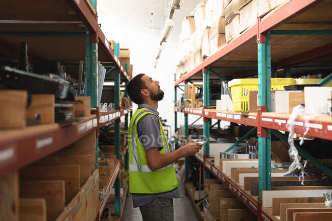 A Caucasian male worker in a storage warehouse at a factory making wheelchairs, standing and inspecting parts on shelves, holding a clipboard — Stock Photo