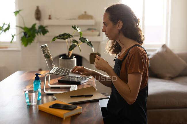 Белая женщина проводит время дома, пьет кофе, работает из дома. Стиль жизни в домашних условиях изоляция в карантинной изоляции во время пандемии коронавируса ковид 19. — стоковое фото