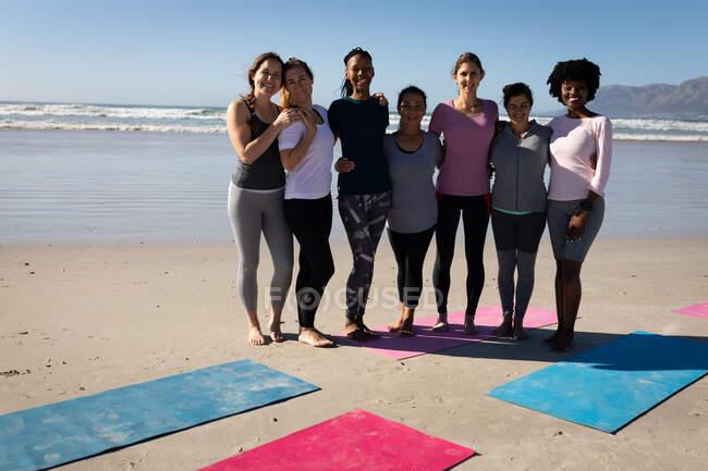 Вид спереди многоэтнической группы подруг, веселящихся вместе на пляже в солнечный день, стоящих за циновками для йоги, одетых в спортивную одежду, улыбающихся. — стоковое фото