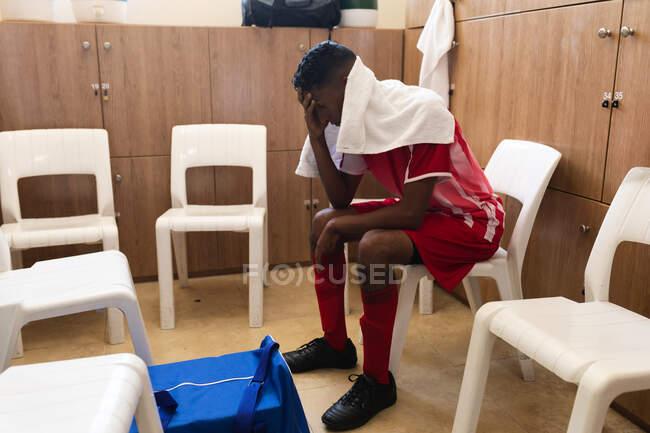 Giocatore di calcio maschile di razza mista che indossa una striscia di squadra seduto nello spogliatoio durante una pausa di gioco, tenendo la testa con un asciugamano intorno alle spalle. — Foto stock