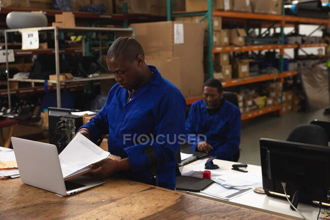 Two African American male workers in a storage warehouse at a factory making wheelchairs, one of them using laptop at a workbench — Stock Photo