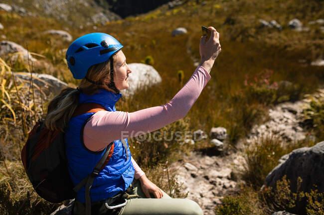 Вид сбоку кавказской женщины, наслаждающейся отдыхом на природе, в тренажерном зале, сидящей, фотографирующей со смартфоном в солнечный день в горах — стоковое фото
