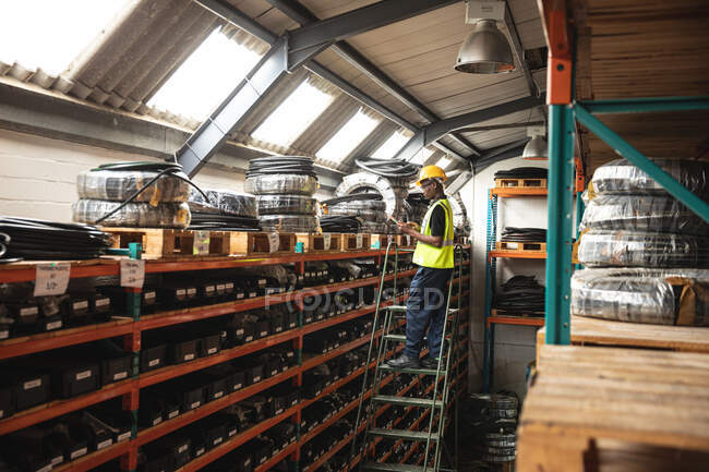 African American male factory worker wearing a high vis vest checking stock standing on ladder. — Stock Photo