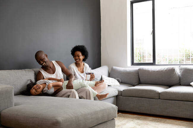 Front view of an African American couple and their young daughter relaxing in the living room together in the morning, the couple sitting on the sofa with the daughter lying across the lap of her father laughing — Stock Photo