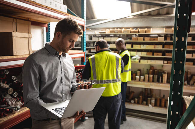 Caucasian male supervisor, African American and Caucasian factory workers wearing a high vis vest checking stock and using laptop. Workers in industry at a factory making hydraulic equipment. — Stock Photo