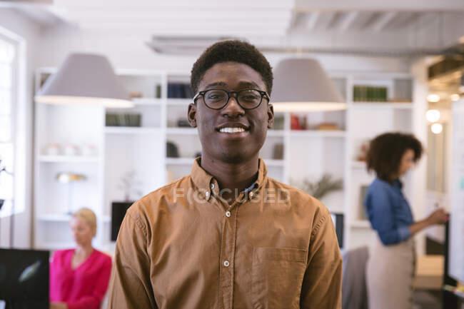 Портрет счастливого афроамериканского бизнесмена, работающего в современном офисе, смотрящего в камеру и улыбающегося, с коллегами по бизнесу, работающими на заднем плане — стоковое фото