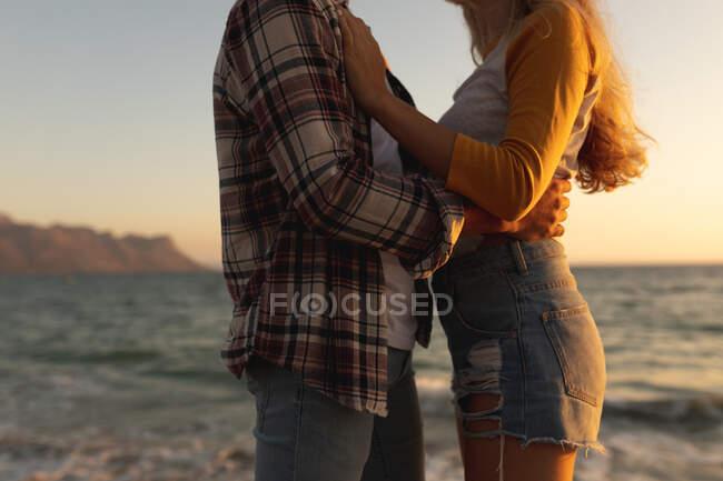 У середній частині пари, що стоїть на набережній біля моря під час заходу сонця, обличчям один до одного і обіймаючи один одного. Романтичні морські канікули — стокове фото