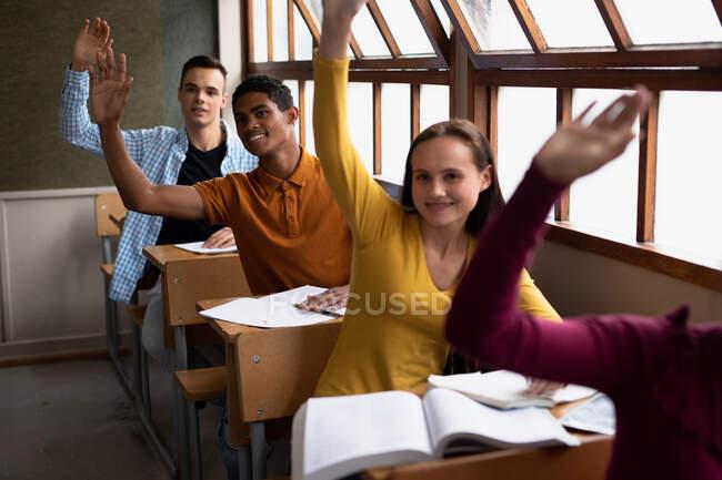 Vista frontal de un grupo multiétnico de adolescentes en una clase de secundaria sentados en escritorios, todos levantando la mano para responder a una pregunta — Stock Photo