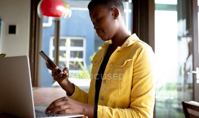 Вид спереди афроамериканки, сидящей в своей гостиной перед окном в солнечный день, используя ноутбук и смартфон — стоковое фото