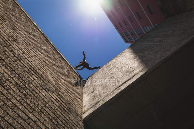 Side low angle view of a Caucasian man practicing parkour by the building in a city on a sunny day, jumping on the rooftop. — Stock Photo