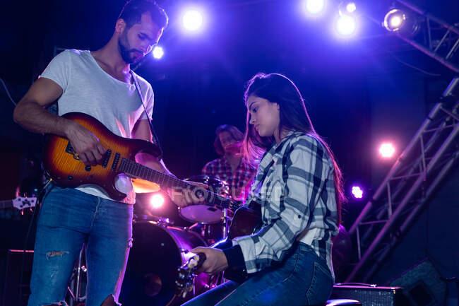 Vista frontal de una guitarrista caucásica femenina y masculina actuando bajo focos en el escenario juntos en un lugar de música, la mujer sentada en un taburete para tocar una guitarra acústica, mientras el hombre toca la guitarra eléctrica de pie - foto de stock
