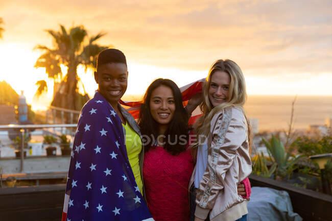 Портрет многонациональной группы друзей, болтающихся на террасе на крыше с закатным небом, смотрящих в камеру и улыбающихся, с американским флагом на плечах — стоковое фото