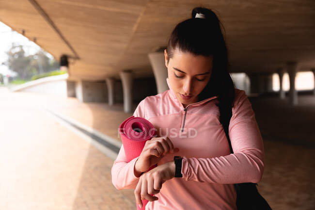 Front view of a fit Caucasian woman on her way to fitness training on a cloudy day, carrying a sports bag and a yoga mat, standing under a bridge, checking her watch — Stock Photo