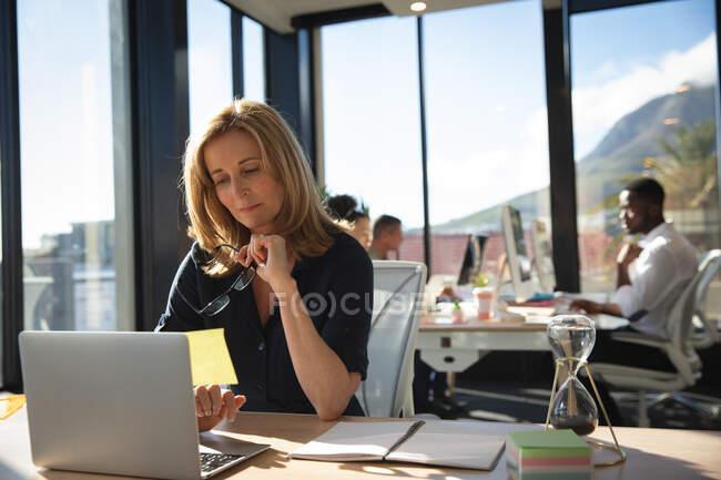 Кавказская деловая женщина, работающая в современном офисе, сидящая за столом и используя ноутбук, со своими коллегами, работающими на заднем плане — стоковое фото