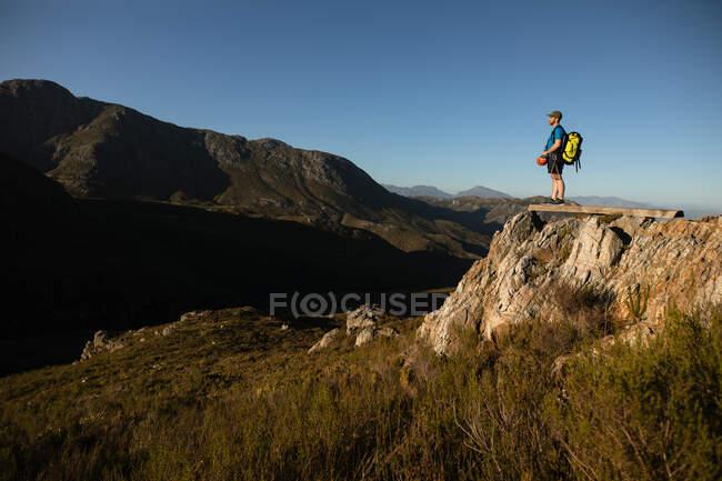 Vue latérale de l'homme caucasien profitant du temps dans la nature, portant un équipement de tyrolienne, randonnée, l'homme se tient debout sur un rocher par une journée ensoleillée dans les montagnes — Photo de stock