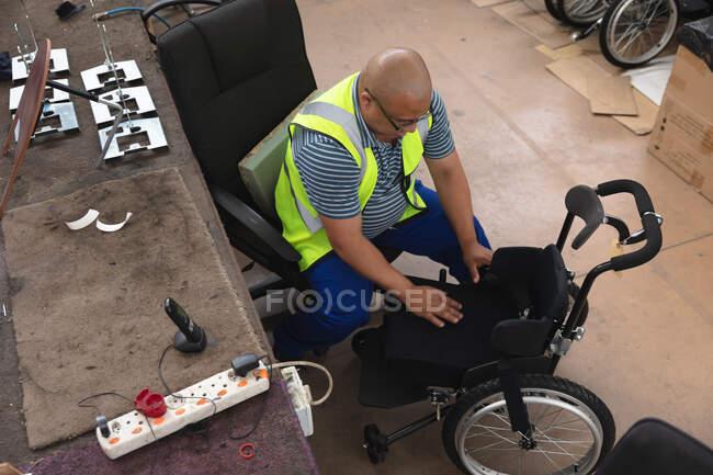 Un ouvrier de race mixte dans un atelier d'une usine fabriquant des fauteuils roulants, assis sur un établi assemblant des pièces d'un produit — Photo de stock