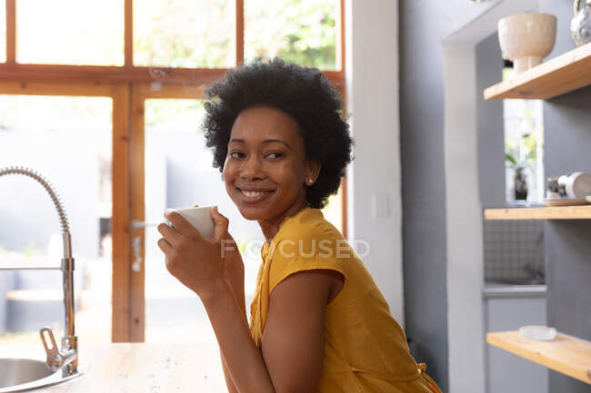 Side view of an African American woman at home, sitting in the kitchen holding a cup of coffee with head turned towards the camera, looking away smiling — Stock Photo