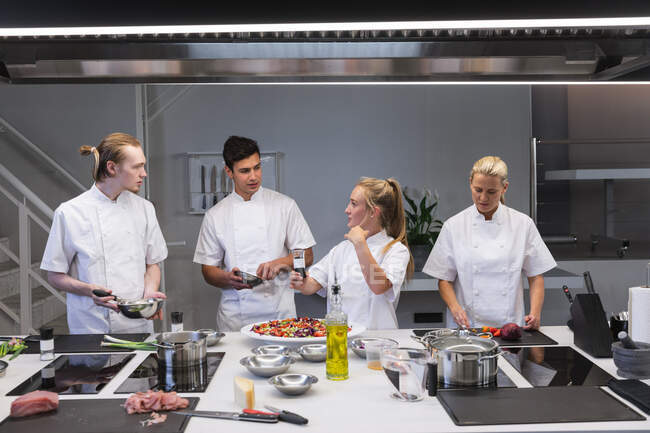 Un grupo de chefs caucásicos cocinando, hablando y mirándose. Clase de cocina en una cocina de restaurante. - foto de stock