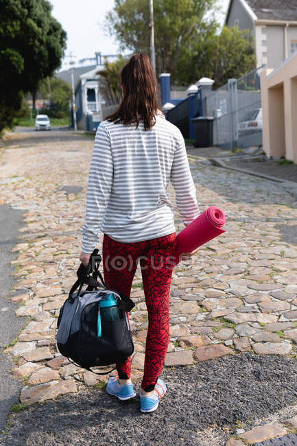 Rear view of a fit Caucasian woman on her way to fitness training on a cloudy day, carrying a sports bag and a yoga mat — Stock Photo