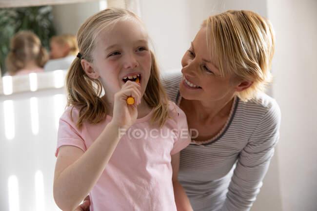 Vista frontal de uma mulher caucasiana desfrutando de tempo em família com sua filha em casa, escovando os dentes e sorrindo em um banheiro — Fotografia de Stock