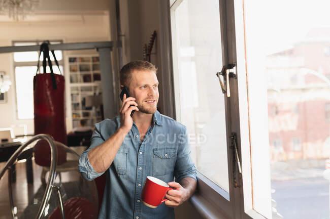 Vista frontale di un giovane caucasico che trascorre del tempo a casa, seduto alla scrivania, parla sul suo smartphone e tiene in mano una tazza di bevanda calda. — Foto stock