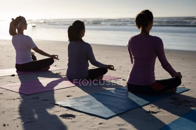 Вид сзади на многонациональную группу подруг, занимающихся спортом на пляже в солнечный день, практикующих йогу, сидящих в позе йоги, медитирующих в позе лотоса, стоящих лицом к морю. — стоковое фото