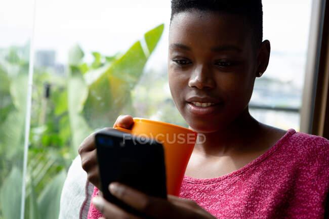 Вид спереди на афроамериканку, сидящую в своей гостиной перед окном в солнечный день, используя смартфон и держа кружку — стоковое фото