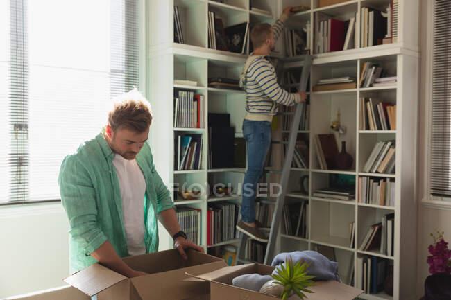 Вид сбоку на пару белых мужчин, въезжающих в новую квартиру, распаковывающих свои вещи из картонных коробок и кладущих их на полки, стоящих на лестнице. — стоковое фото