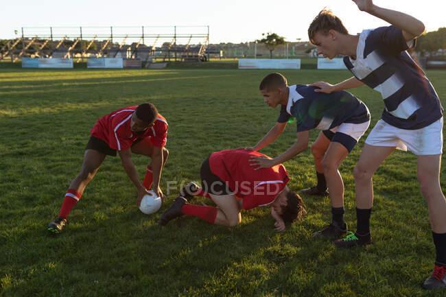 Vue latérale de deux équipes masculines multiethniques adolescentes de joueurs de rugby portant leurs bandelettes d'équipe, en action lors d'un match sur un terrain de jeu, aidant un joueur blessé tombé au sol — Photo de stock