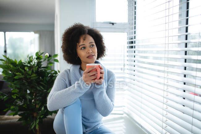 Вид спереди женщины смешанной расы, расслабляющейся дома, сидящей на подоконнике, выглядывающей в окно, держащей чашку кофе и улыбающейся — стоковое фото