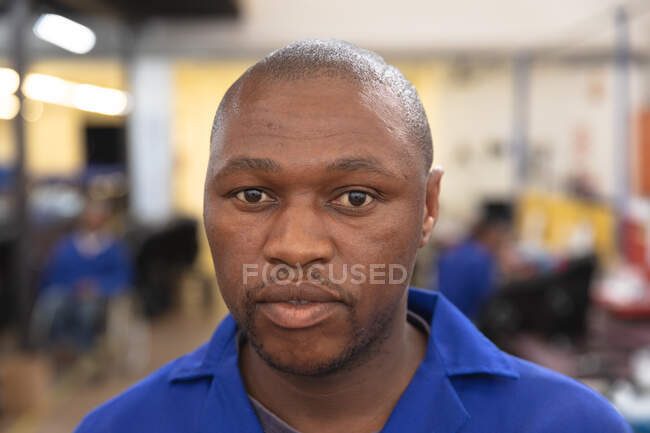 Portrait of an African American male worker wearing a workwear, in a storage warehouse at a factory making wheelchairs, looking at camera — Stock Photo