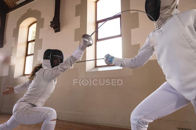 Кавказские и афроамериканские спортсменки во время тренировки по фехтованию в защитных костюмах целятся друг в друга своими эпинефринами. Обучение фехтовальщиков в спортзале. — стоковое фото