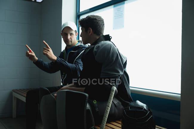 Побочный вид подростка-хоккеиста и его кавказского тренера, сидящего в гримерке и говорящего об игре — стоковое фото