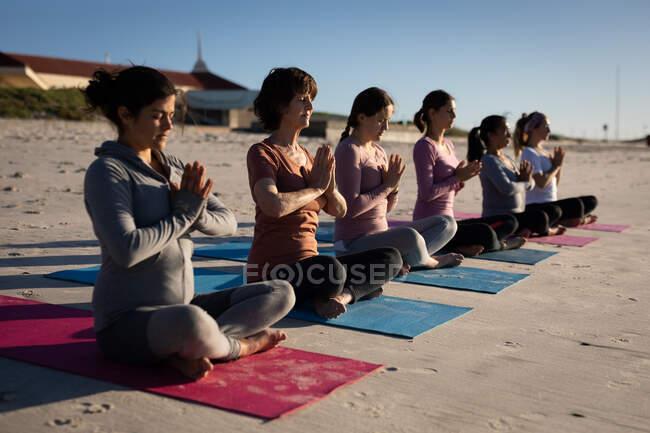 Вид сбоку на многоэтническую группу подруг, наслаждающихся упражнениями на пляже в солнечный день, практикующих йогу, сидя в позе йоги в ряд, посредничающих с закрытыми глазами и руками в позе йоги. — стоковое фото